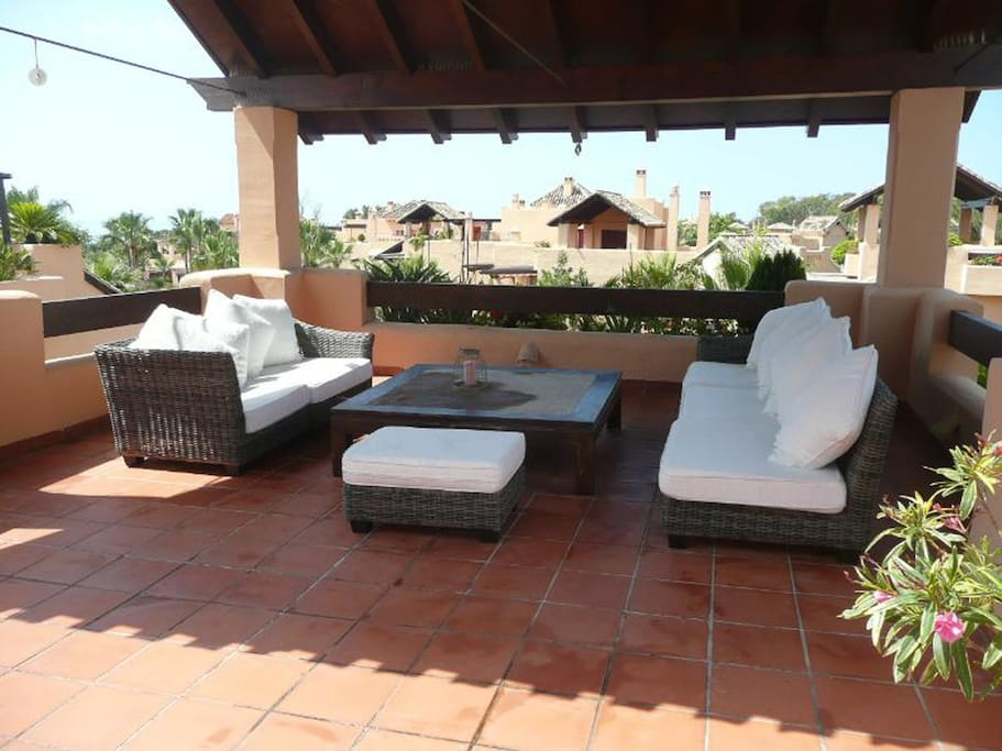 Covered area with lounge seating on the rooftop terrace