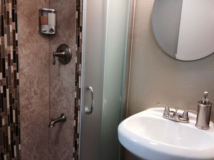 Brand new stand up shower with sliding glass door and vanity.