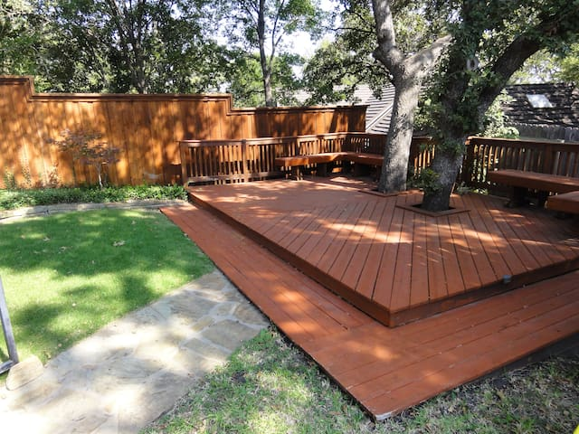 Relax on the bench seats under the oak trees growing from under the deck.