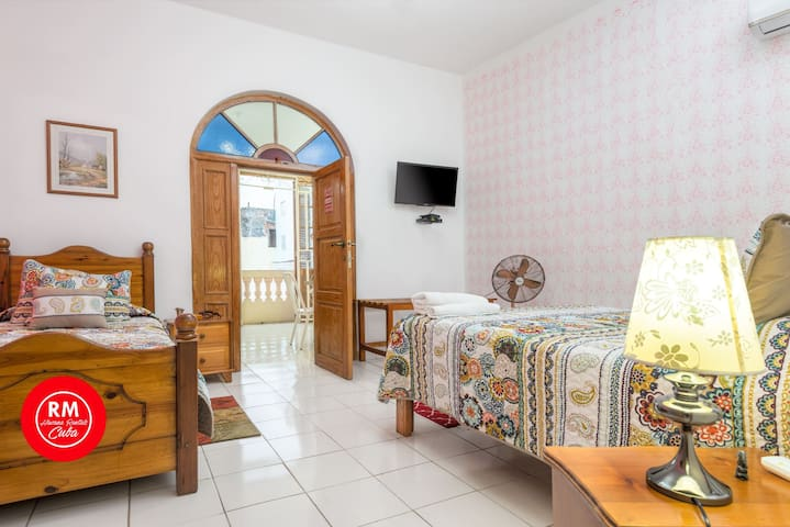 Bedroom 2 next to the living with double bed and single bed air conditioner and tv with a safe for documents and money