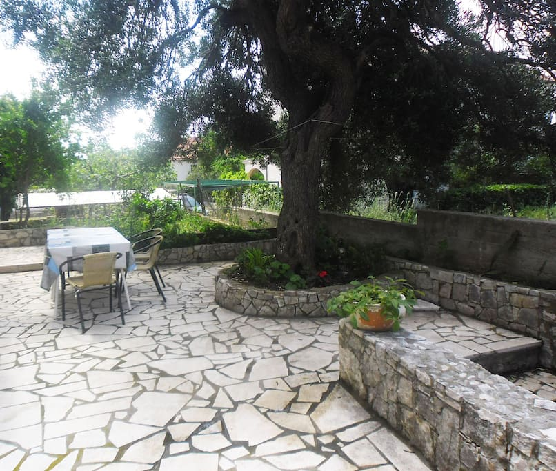 In front of the apartment! Very nice place to sit and rest in the shadow of the big olive tree.