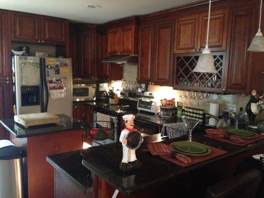 Fully equipped kitchen including range, oven, microwave oven, toaster oven, dishwasher, and refrigerator / freezer.