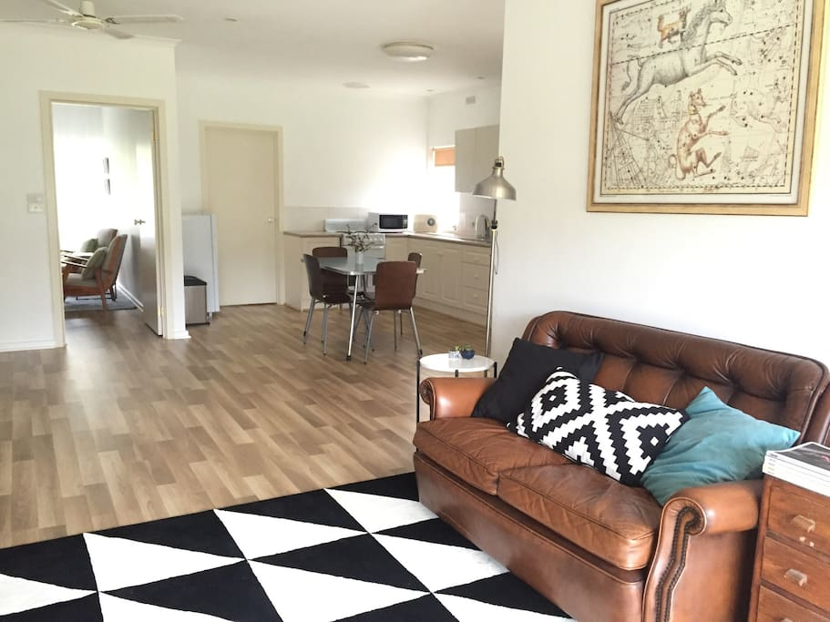 Comfortable chairs and TV in lounge, lead into the self-contained, open plan kitchen area