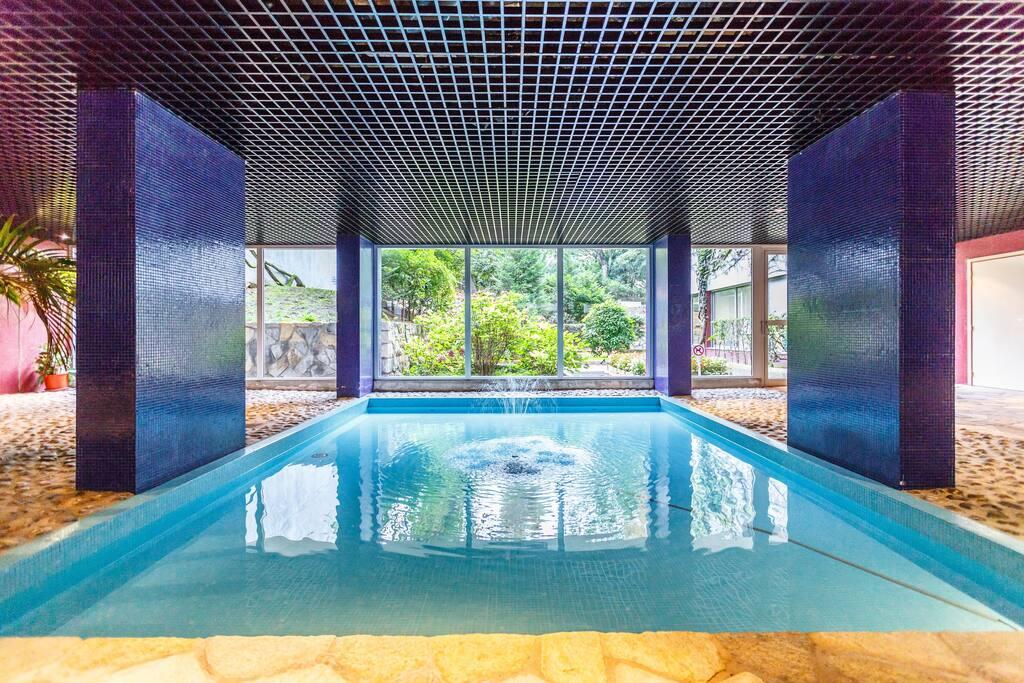 Hall d'entrée avec bassins et vue sur jardin privé de l'immeuble