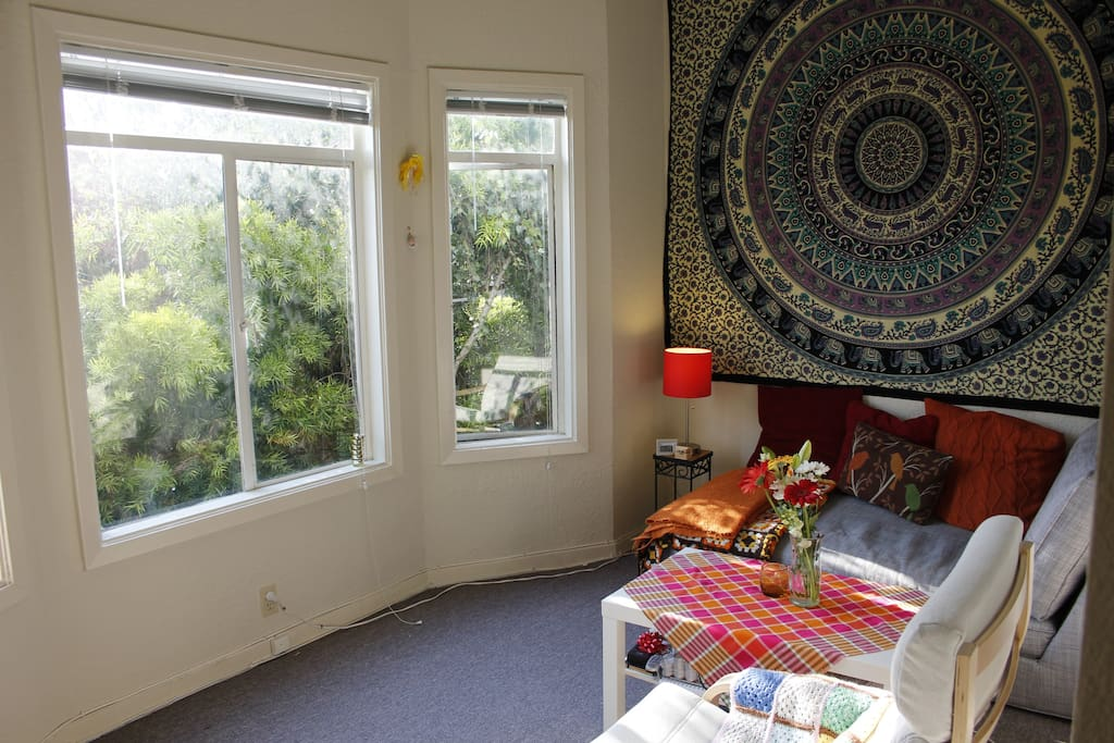 Living room has nice, bright windows with trees outside!