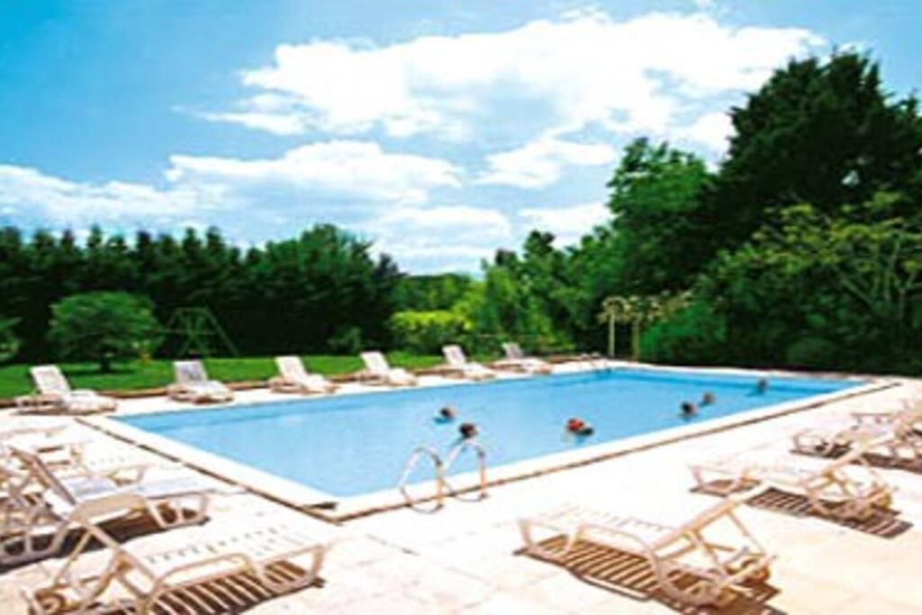 La piscine avec espace vert et jeux d'enfant.