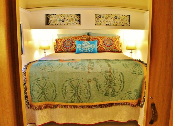The Happy Camper is glamper-style featuring a private bedroom, queen bed w/ lots of pillows, big windows, ample space for bags.  The camper has heat and air, but you might want to crank open the upper fan and enjoy the breeze. You'll sleep hard here.