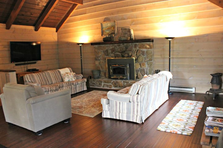 Our cozy Great Room featuring a stone fireplace, and new wood floor (6/2016)