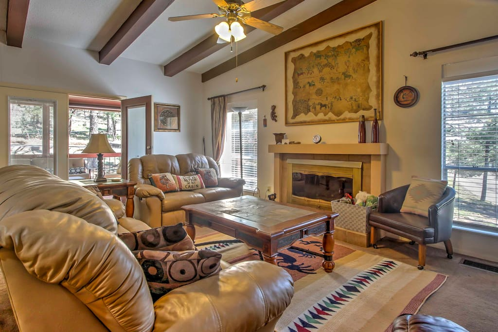 The interior is embellished with wooden beams, a beautiful fireplace, and plush leather furnishings.