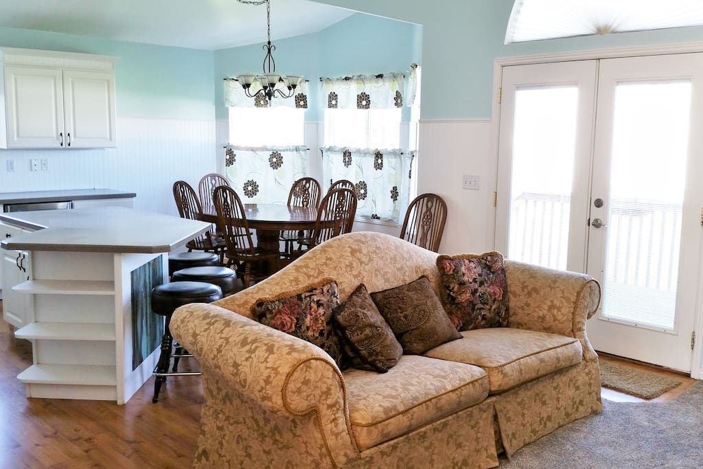 Large kitchen table with seating for 7, plus 4 oversized cushy barstools at the island. French doors to deck and patio.