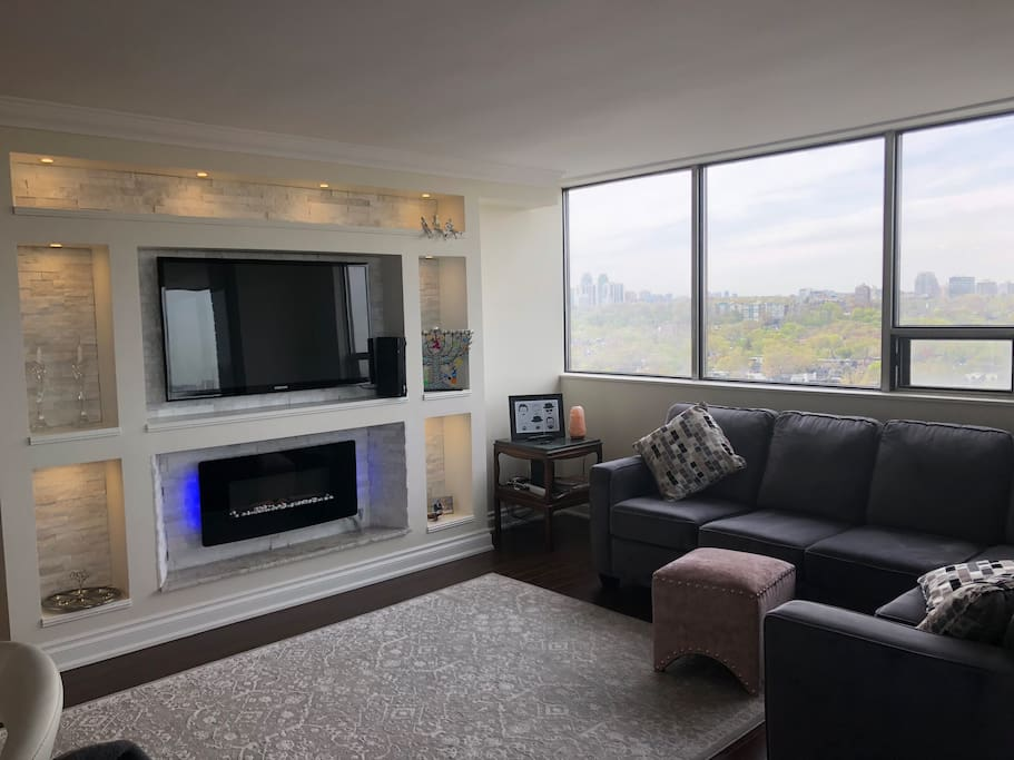 Entertainment centre and living space with fireplace and unobstructed views of downtown Toronto