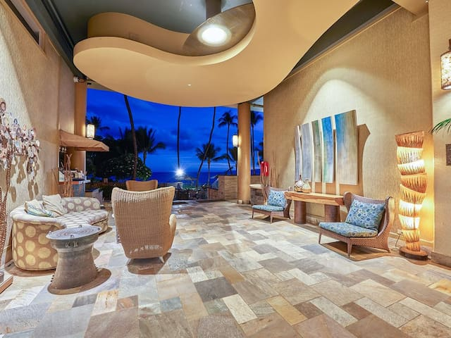 Open air lobby provides direct access to the pool, grassy grounds, and beach.