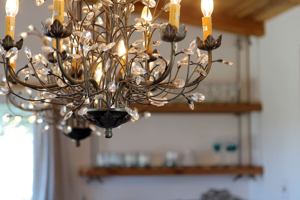 Double crystal chandelier over custom rustic dining table open to the living room.
