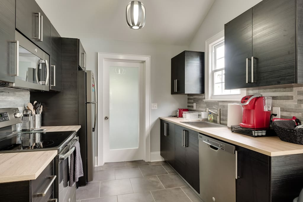 Stainless steel appliances with Ikea cabinets. Washer and dryer are in the utility room off the kitchen. Fridge is always stocked with soda and water.