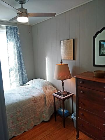 Bedroom 3 contains single bed, dresser, night stand & lamp, ceiling fan, and floor fan.