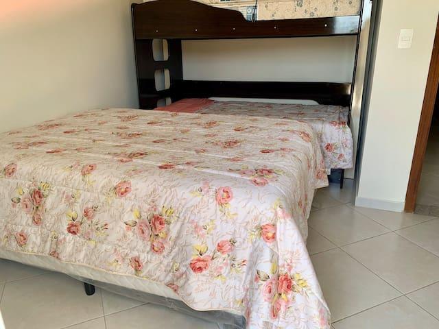 Quarto 4- cama de casal, beliche e ventilador de chão. Esse quarto tem um banheiro exclusivo no hall dos quartos.  Ele tem acesso à varanda superior, com vista para piscina e quadra.