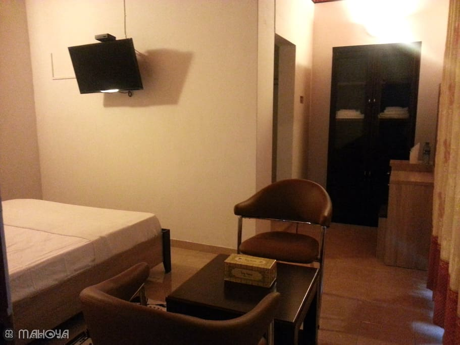 Room is equipped with a glass door wooden cupboard, a dressing table, a coffee table with two chairs, and a LED TV.