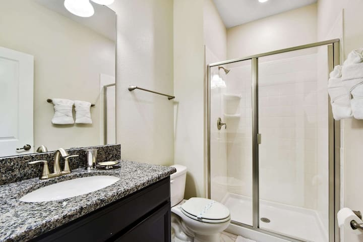 This 1st floor family bathroom is adjacent to the king bedroom and offers tiled floors, mirrored vanity unit with sink, toilet and walk-in shower.