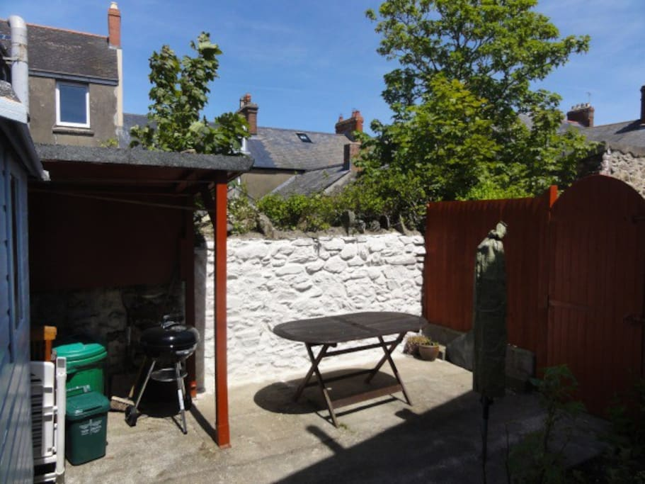 Patio area sun trap.  Table and chairs, bbq, logs & composter.