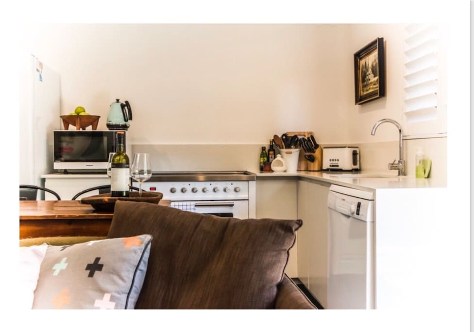Well stocked kitchen with 90cm Ilve stove and two seat dining area
