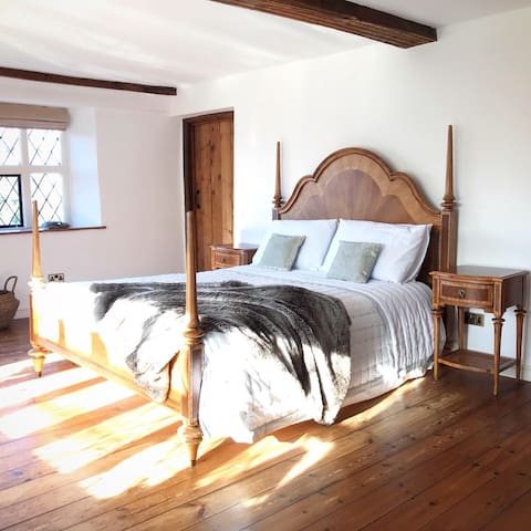 Master bedroom with ash and walnut wood four poster king bed