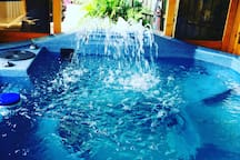 Hot tub has waterfall.