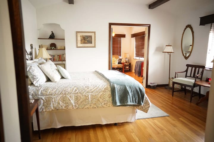 Master bedroom has a super comfy bed, seating and attached bathroom