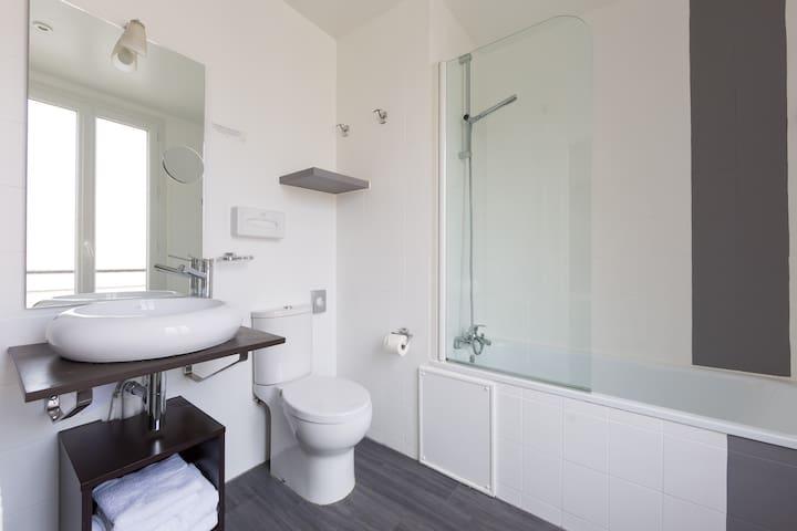 Salle de bain privative avec toilette, serviettes, sèche cheveux, savon, gel douche, baignoire.