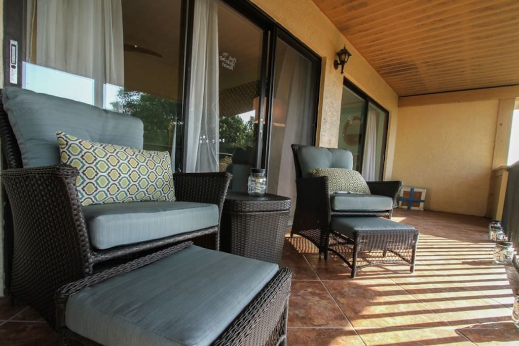 Tastefully decorated balcony seating area with matching chairs & ottomans