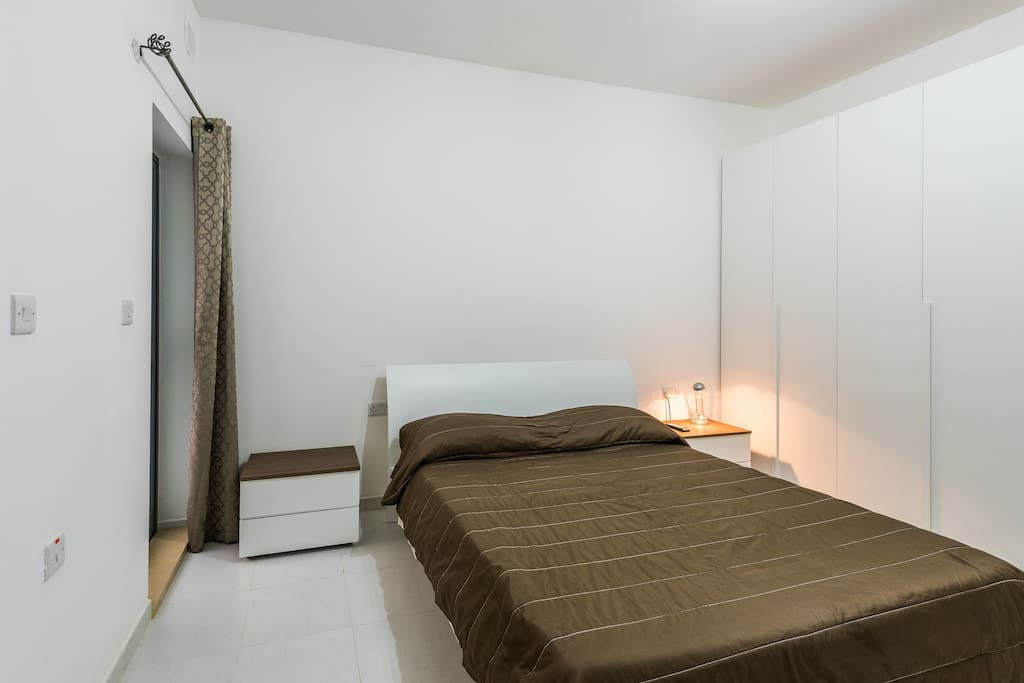 Ensuite king size bedroom with ample storage - 3 compartments wardrobe as well as large chest of drawers. The room is equipped with AC - heating / cooling.  Towels and bed linen provided.