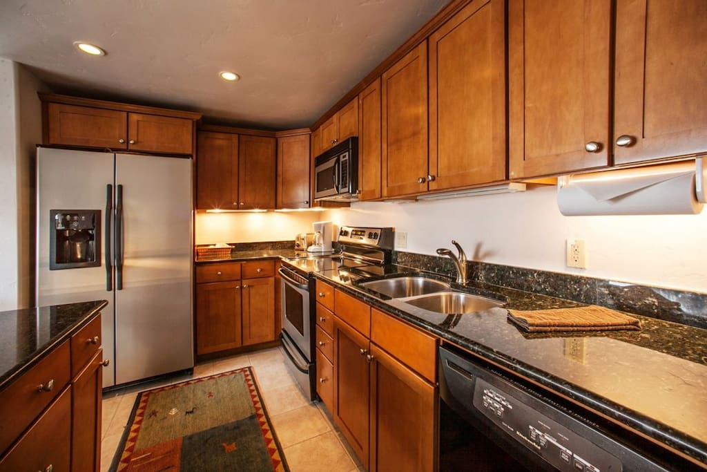 Open kitchen with granite counter tops and stainless steel appliances.