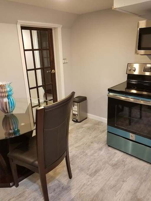 This is a partial view of the kitchen and dining area. It's a eat in kitchen with a refrigerator stove and cupboards and microwave. Kitchen is also equipped with plates, pots and utensils.