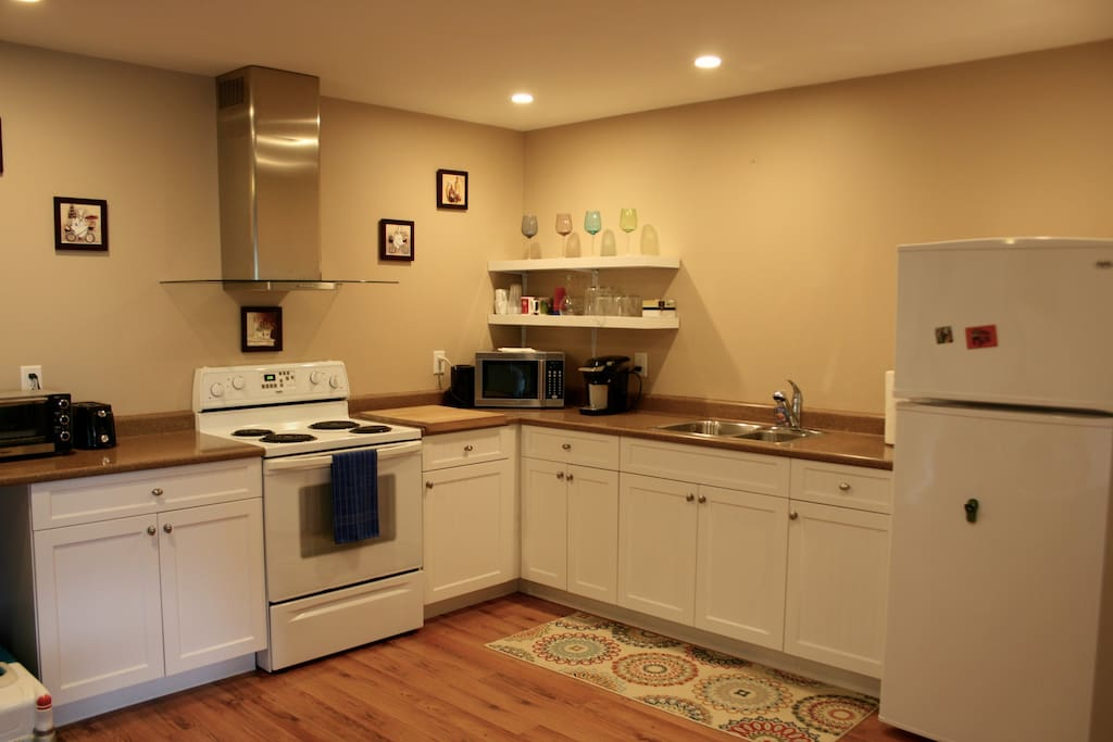 Kitchen has oven/stove, microwave, fridge, toaster oven, coffee maker, kettle, cooking utensils, dishes, pots/pans.