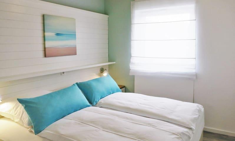 Helles, modernes Schlafzimmer mit Komfort-Boxspringbett
