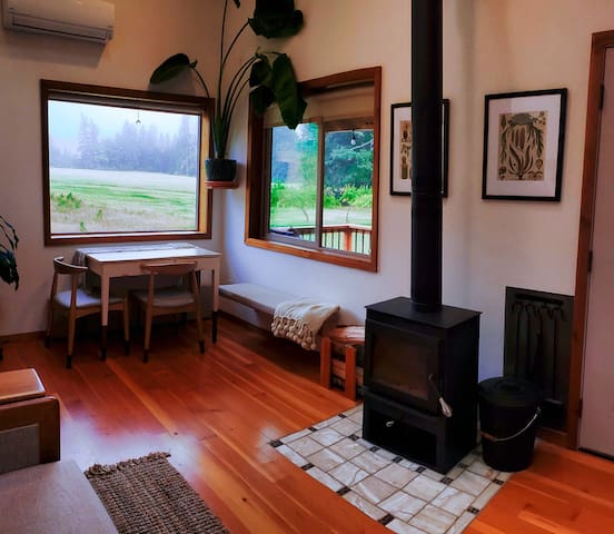 Main Room with expandable dining table, picture windows, and wood stove