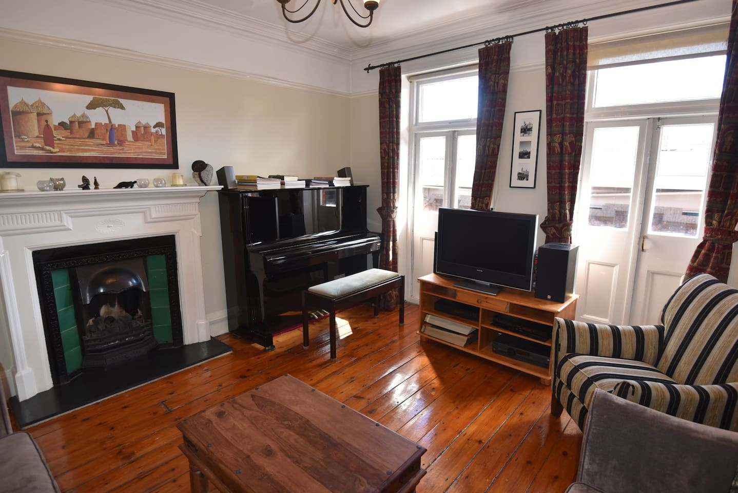 Living room with period fireplace and features, wooden floors, and doors opening onto balcony