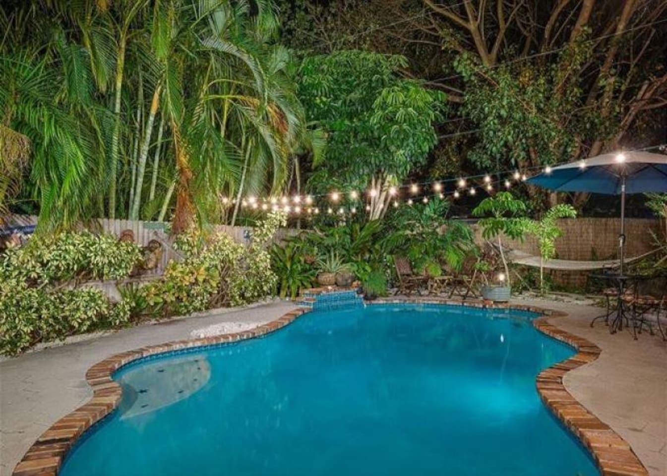 Evening Poolside offers a serene ambient effect with lighting and tropical plants surrounding the pool and sitting area.