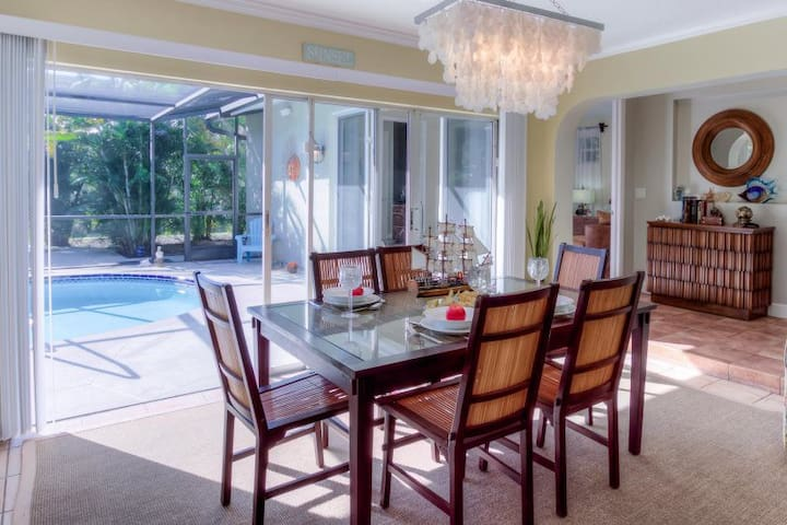 Formal dining room with pool and garden view.