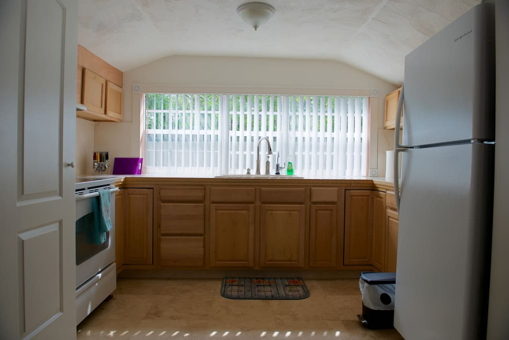 Full kitchen with dining ware, cooking utensils and dining table for two.