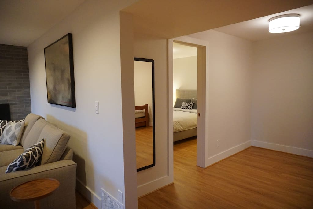 Common area leading to bedroom #1 with queen bed.
