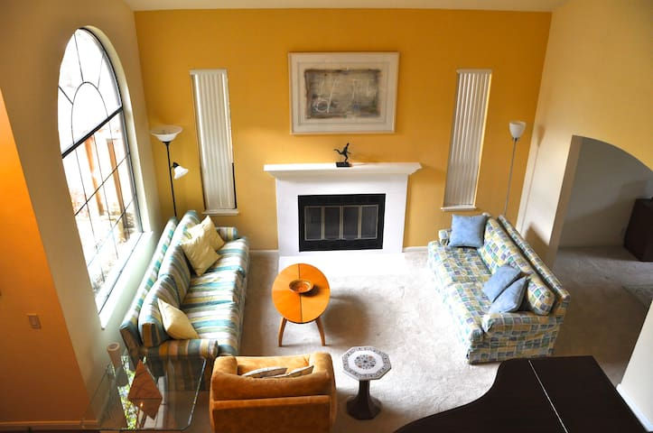 Bright and modern living room, with high ceilings and thick new carpeting.
