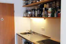 Kitchen includes fridge, freezer, oven, stove and many utensils.