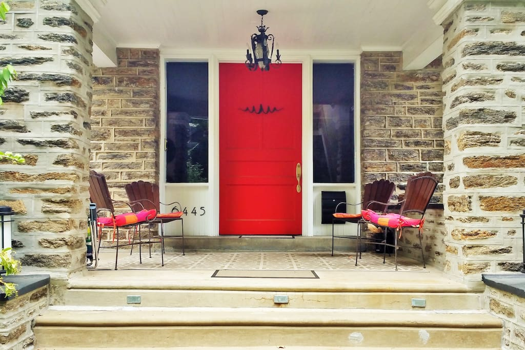 Front porch, red entrance door, stone exterior.