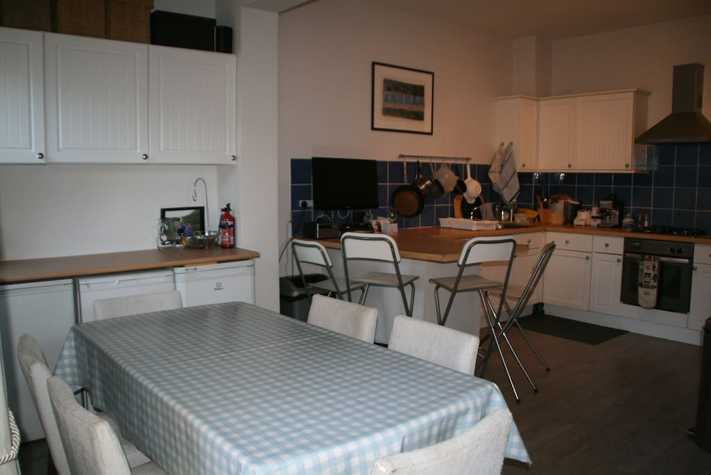 Kitchen, including a break bar seating area with four stools, as well as a table with six chairs.