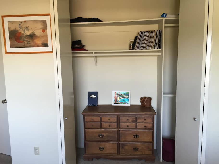 Spacious folding door closet with shelves, dresser, and bars for hanging  clothes.