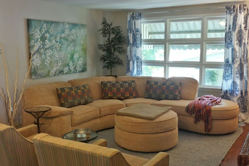 View of the spacious living room with lots of seating and natural light.