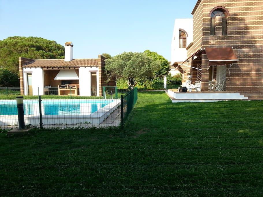 Amplio jardín con terraza, piscina y paellero/barbacoa.