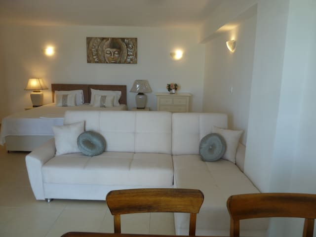 Comfortable, spacious seating section of studio facing double balcony door which lead out to veranda and the pool area.