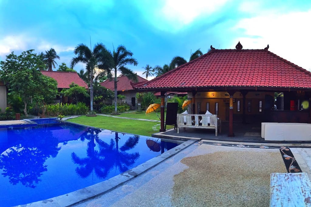 Out door pool surrounding with green garden and confy to spend your holidays in Bali