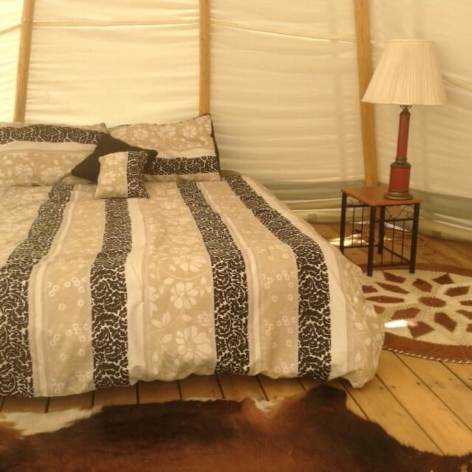 There is a queen size bed in each Tipi . They have a lamp ,and a cot can be brought in for a child to sleep in